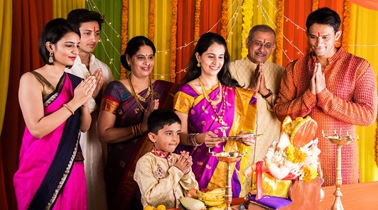 cheerful indian family celebrating or praying Lord Ganesh or ganpati bappa on ganesh festival or ganapati festival or ganesh utsav or ganeshotsav at home with puja thali