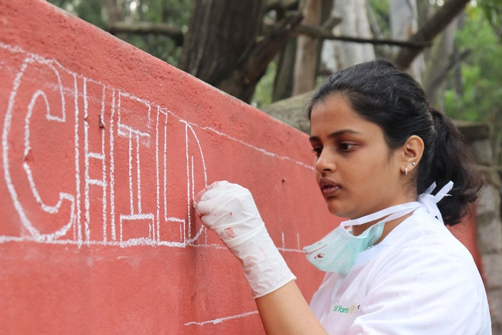 A student of Christ University creating graffitti